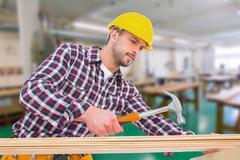 Composite image of handyman using hammer on wood Stock Photos