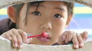 Stock Video Footage of Cute Little Asian Girl Peeking Through Hole In Wall