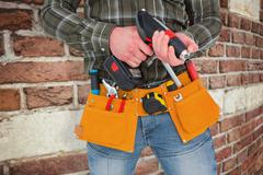 Composite image of manual worker holding gloves and hammer power drill Kuvituskuvat