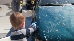 Toddler helping mother wash car Stock Footage