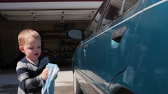 Mother washing car with her toddler Stock Footage