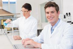 Scientist working attentively with laptop and another with beaker Stock Photos