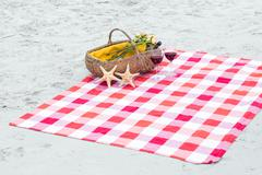 Picnic basket with glasses of red wine and starfishes on a blanket - stock photo