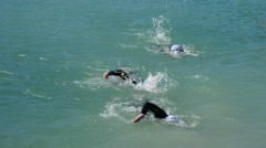 Swimmers coming to shore in a triathlon Stock Footage