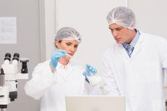 Scientists working attentively with beaker Stock Photos