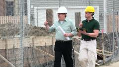 Contractors consulting at housing development Stock Footage