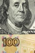 A fragment of one hundred dollars and one hundred rubles - stock photo