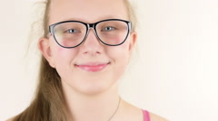 Big blue eyed, weared glasses teenage girl smiling in studio Stock Footage