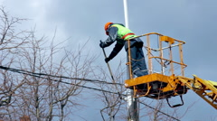 Worker in Cradle of Skylift Colors Lamppost With White Paint Stock Footage