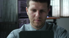 Young man working on a tablet in a modern business environment Stock Footage