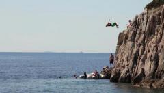 Man jumping of the cliff into the ocean double Backflip Stock Footage