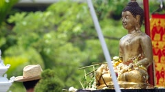 People give the flowers to Buddha statue Stock Footage