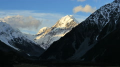 New Zealand Mt Cook cloud approaches sunlit peak Stock Footage