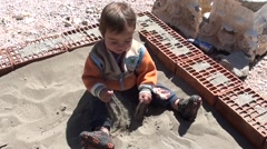 Child throws sand on himself Stock Footage