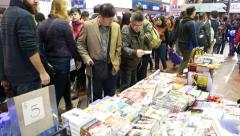 Focusing on two man looking up book stall on busy night street Stock Footage
