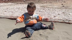 Toddle enjoys playing with sand- Stock Footage
