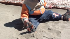 Toddle plays with sand zoom out Stock Footage