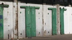 Green doors + zoom out loading platforms and storage compartments warehouse Stock Footage