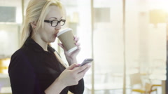 Blond Girl is using Mobile Phone and Smiling - stock footage