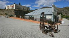 New Zealand Old Cromwell historic building and antique farm machine - stock footage