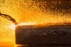 Industry steel, Slab scarfing, Tending the fire spread from the open shell slab. - stock photo