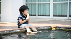 Little asian boy eating melon and splashing around in the pool Stock Footage