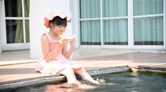 Little asian girl eating melon and splashing around in the pool Stock Footage