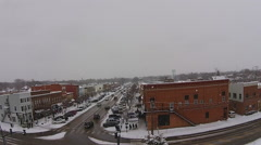 Vehicles traveling through historic downtown on a snowy Ohio Day Aerial View Stock Footage