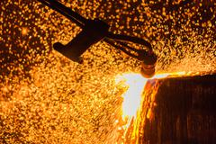 Industry steel, Slab scarfing, Tending the fire spread from the open shell slab. Stock Photos