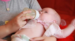 PEOPLE. CHiLDREN-2012: Small baby drinking milk from a bottle on the mothers Stock Footage