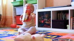 PEOPLE. CHILDREN-2012: Small baby read books on the floor Stock Footage