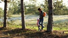 Mother and child daughter walking in a pine forest - stock footage