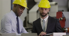 Managers discuss business at a busy production factory Stock Footage