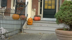 Pumpkins on the porch with a tree in the foreground. - stock footage