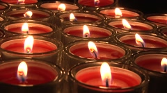 Close up of large group of red tea candles on rotating display Stock Footage