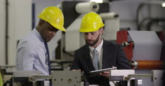 Worker and foreman in a safety hats performing quality check in a factory. Stock Footage