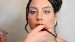 Make up artist applies Lip stick to female model Stock Footage