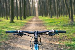 Mountain biking down hill descending fast on bicycle. View from - stock photo
