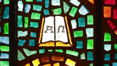 Dolly across Alpha Omega book stained glass Stock Footage