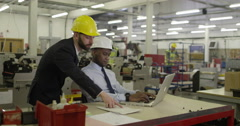 Manager and foreman working on a laptop in a factory discussing business. Stock Footage