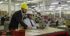 Manager and foreman in a factory discussing inventory. Stock Footage