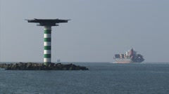 Container ship Maule outbound + beacon + zoom out harbour mouth Stock Footage