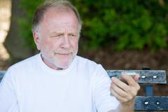 Closeup portrait of funny elderly man in white shirt, skeptical, checking sma - stock photo
