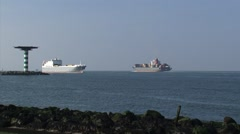 Sea vessels inbound and outbound behind Maasmond beacon - stock footage