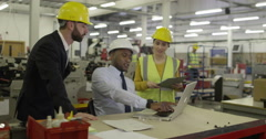Workers look at laptop computer in shipping warehouse. Stock Footage