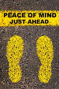 Conceptual image with yellow paint footsteps on road behind motivational message - stock photo