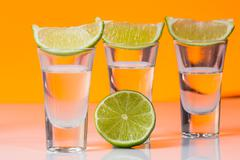 Tequila shot with a slice of lime on the glass orange background - stock photo