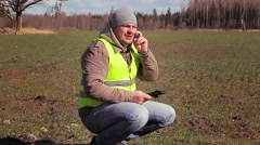 Farmer with cell phone and tablet PC on the sown field Stock Footage