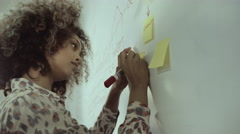 Woman writing on adhesive note - stock footage