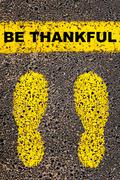 Conceptual image with yellow paint footsteps on road behind motivational message Stock Photos